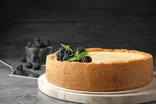 Delicious cheesecake decorated with blackberries on table