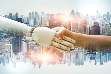The double exposure image of a human hand and a robot hand shaking hands. Blurred cityscape background. Concept of innovation and social in city. Toned image double exposure.