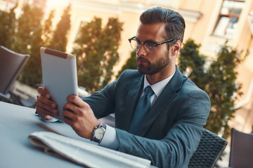 Modern businessman. Portrait of handsome bearded businessman in eyeglasses working with touchpad...