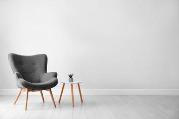 Fototapeta Stylish room interior with comfortable armchair near light wall, space for text obraz