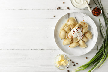 Delicious cooked dumplings with sour cream on white wooden table, flat lay. Space for text