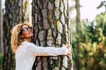 Happy beautiful woman love nature hugging a pine tree - no deforestation concept and earth's day...