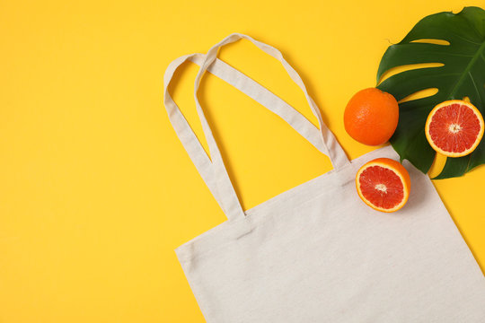 Eco bag, palm leaf and orange on color background, copy space