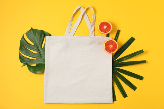 Eco bag, palm leaves and orange on color background, copy space