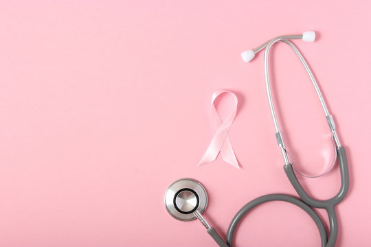 Pink ribbon on a colored background top view. Cancer disease.