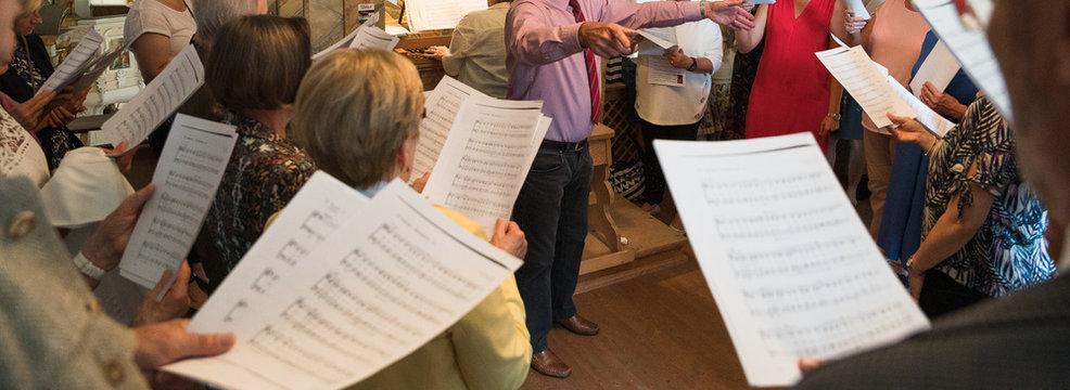 Probe bei einem Kirchenchor mit Notenblättern und Dirigenten