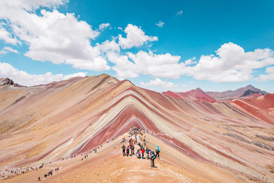 Vinicunca Rainbow Mountain, tourists standing on top of the mountain and admiring the view, Cusco, Peru
