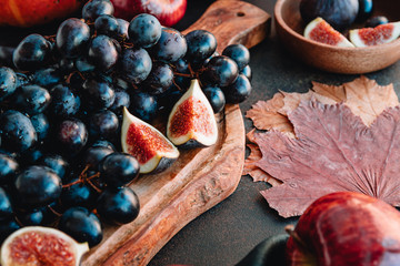 Autumn food still life with season fruits and vegetables like Bangalore blue grape, red apples and figs on a table.