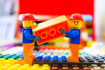 Two Lego construction workers carrying together a orange brick on March 14, 2019 in Poznan, Poland.