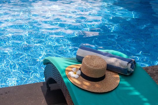 Exotic frangipani flower and hat next to the pool
