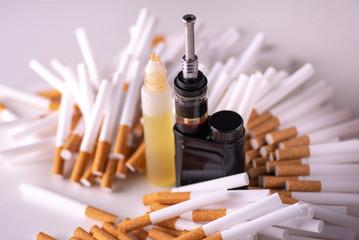 Pile of cigarettes and modern electronic cigarette. vape vs cigarettes