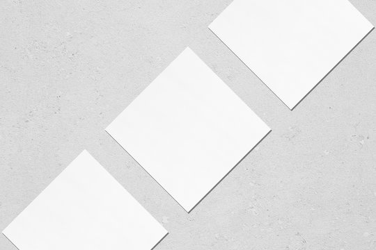 Three empty white square business card mockups with soft shadows lying diagonally on neutral light grey concrete background. Flat lay, top view. Open composition.