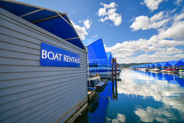 Boats line up in their covered boat slips at a marina next to a boat rental sign in the Pacific Northwest