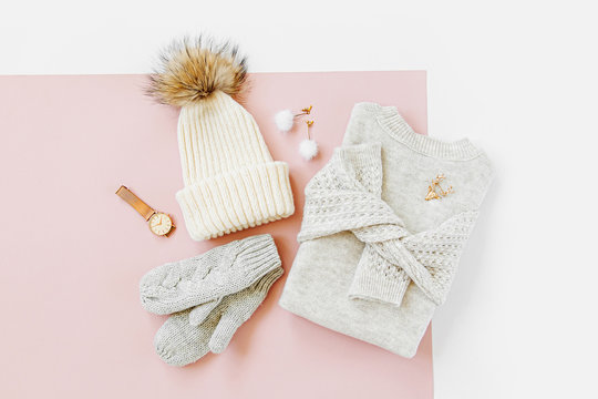 Gray warm knitted sweater with winter hat, mittens on pale pink background. Women's stylish winter clothes. Flat lay, top view.