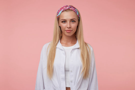 Beautiful young woman with long blond hair looking at camera with soft smile, wearing colored headband and white shirt, standing over the pink background