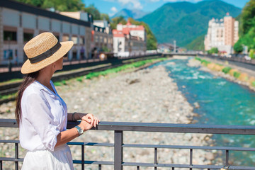 Happy girl at hat on the embankment of a mountain river in a European city. Wall mural