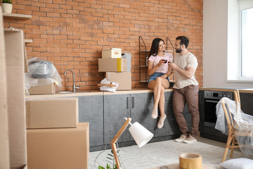 Happy young couple drinking wine after moving into new house