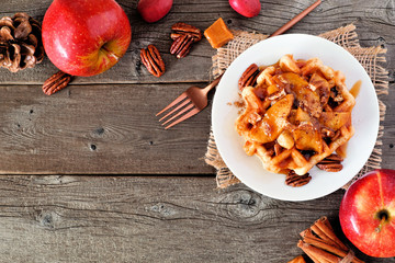 Sweet breakfast waffle with baked apple, pecans and caramel. Top view corner border with copy space over a wood background. Autumn food theme.