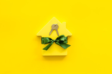 Buying a new house concept with house figure and keys on yellow background top view