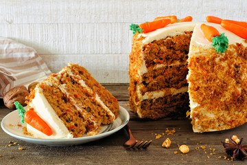 Slice of homemade carrot cake with cream cheese frosting and fondant carrots. Side view table scene with a white wood background.