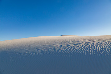 Rippled sand dunes at White Sands National Monument in New Mexico, with a blue sky overhead