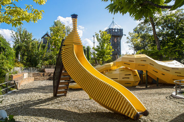 The Gathering Place - Award winning public theme park in Oklahoma - Yellow banana shaped slide and snake climbing tunnel with Play castle in background