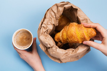 Breakfast to go - croissants and coffee with milk on blue background. Top view