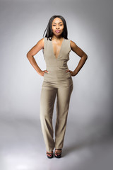 Beautiful black African American fashion model posing with humus grey or khaki clothing in a studio for fall collection catalog.  She is confidently showing the sleeveless top and matching pants.
