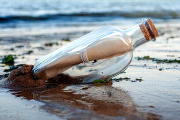 Asking for assistance, optimism and survivor desperation to contact the world conceptual idea with a message in a glass bottle with a cork washing away on sandy beach with the ocean in the background