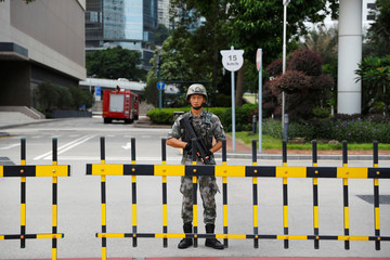 A Chinese PLA soldier guards the entrance to the PLA Hong Kong Garrison headquarters in the Central Business District in Hong Kong