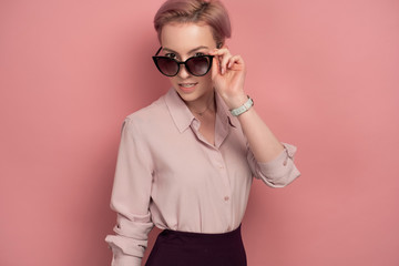 A girl with short pink hair in a blouse and skirt stands on a pink background, looking over sunglasses.
