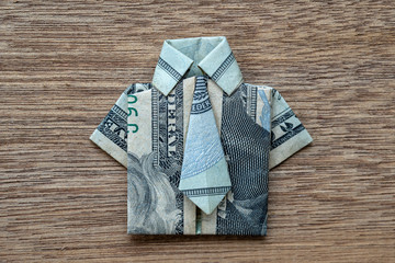 Origami shirt made of dollar banknote on wooden background. Closeup. Dollar bill T-shirt