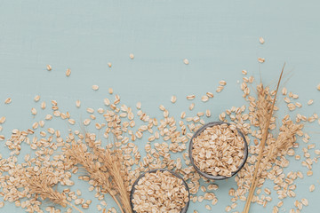 Dry oatmeal flakes with ears of wheat on light blue background. Wheat seed background.