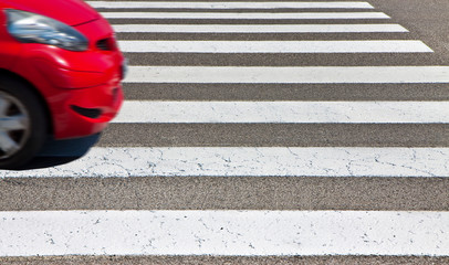 Black and white pedestrian crossing with red car on background - image with copy space - The car's shape has been modified and is not recognizable