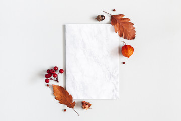 Autumn composition. Paper blank, flowers, leaves on gray background. Autumn, fall, thanksgiving day...