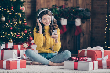 Full length body size photo of charming cute nice girl wearing yellow jumper denim knitted toothily smiling watching something on phone while listening to audio