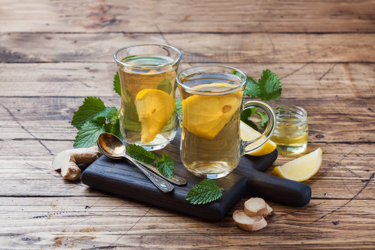 Two cups of natural herbal tea ginger lemon mint and honey on a wooden background. Copy space