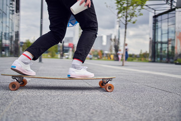 Picture of legs of girl in black jeans riding skateboard on street in city