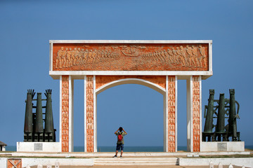 A man takes a photo beneath the monument at the site of the 'Point of No Return' where slaves were loaded onto ships in the historic slave port of Ouidah