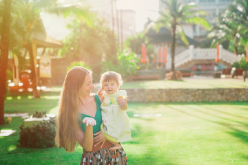 the child in the arms of the mother. Woman throws baby up. holiday, travel, family day concept