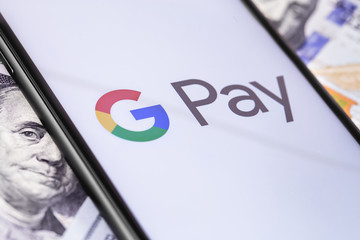 money, dollars and smartphone with Google Pay logo on the screen. Google Pay is a mobile payment and digital wallet service by Google. Moscow, Russia - March 12, 2019