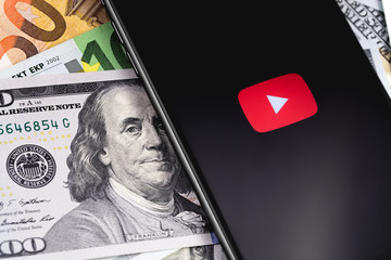 money, YouTube logo on the screen smartphone. YouTube is a free video sharing application that anyone can watch. Moscow, Russia - March 15, 2019