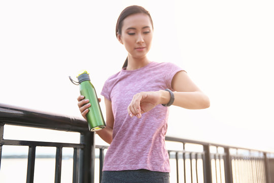 Sporty Asian woman with fitness tracker and bottle of water outdoors