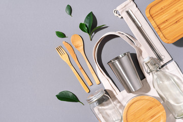 Cotton bags, glass jar, bottle, metal cup, straws for drinking, bamboo cutlery and boxes on gray background. Sustainable lifestyle. Zero waste, plastic free shopping concept.