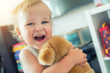 Cute adorable caucasian blond toddler boy having fun, laughing and hugging soft puppy toy indoors. Cheerful child playing with teddy bear at home. Kid friend animal toy. Happy childhood concept