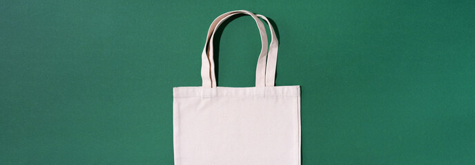 Canvas tote bag canvas and linen fabric bags with drawstring on green background with copy space. Top view. Zero waste, plastic free concept. Eco friendly shopper.