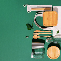 Sustainable lifestyle. Zero waste, plastic free shopping concept. Cotton bags, glass jar, bottle, metal cup, straws for drinking, bamboo cutlery and boxes on green background