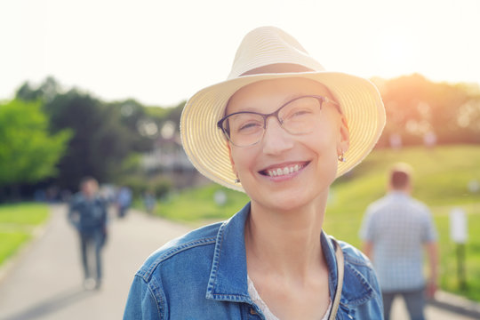 Happy young caucasian bald woman in hat and casual clothes enjoying life after surviving breast cancer. Portrait of beautiful hairless girl smiling during walk at city park after curing disease