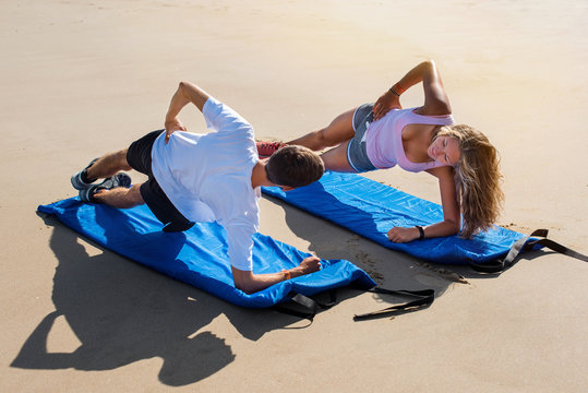 young couple doing pilate on the sunny beach