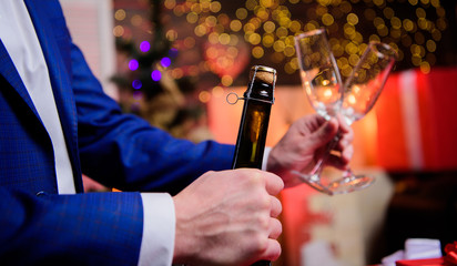 Lets celebrate. Male hands opening champagne bottle pouring glasses christmas decorations background. Drink champagne or sparkling wine. Celebrate new year with champagne. Toast and cheers concept